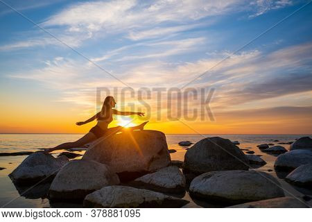 Side view of flexible female doing splits on rocky seashore against cloudy evening sky with bright sun