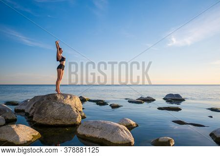 Full length fit female in underwear standing on rock in Urdhva Hastasana pose against sundown sky during yoga lesson near sea in evening
