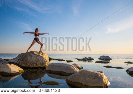 Full length fit woman in underwear doing splits on rocks near calm sea during sunset