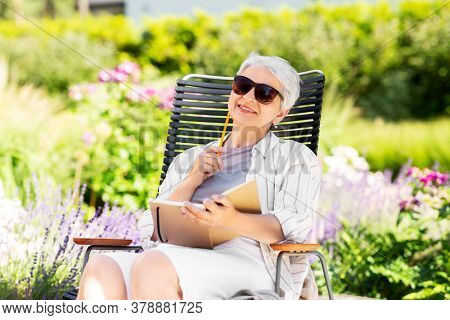 old age, retirement and people concept - happy senior woman with diary sitting in chair at summer garden