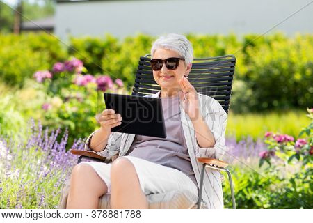 technology, old age and people concept - happy smiling senior woman with tablet pc computer having video call and waving hand at summer garden