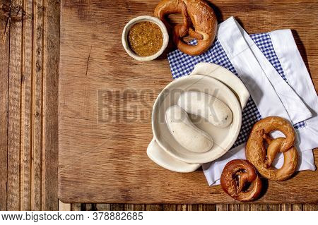 Munich Bavarian Traditional White Sausages In Ceramic Pan Served With German Sweet Mustard And Pretz