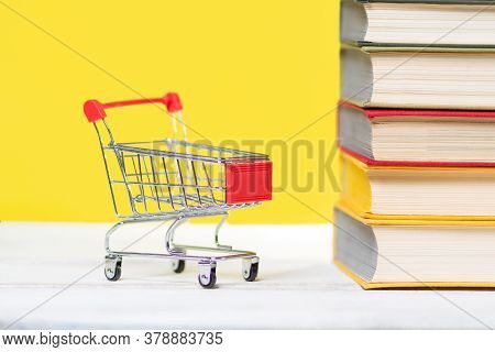 Back To School. A Mini Shopping Cart And A Stack Of Books With An Open Book At The Top On A Yellow B