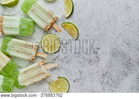 Delicious lime and cream homemade popsicles or ice creams placed with ice cubes on gray stone backdrop. Flat lay, top view with copy space