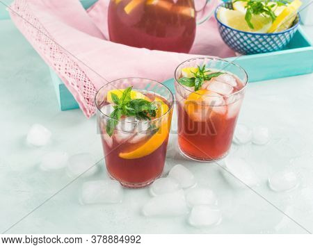 Fresh Red Cocktail Mocktail Sangria In Pitcher And Glasses With Ice, Mint Leaves And Lemon And Orang