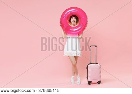 Excited Tourist Woman In Summer Dress Hat With Suitcase Isolated On Pink Background. Traveling Abroa