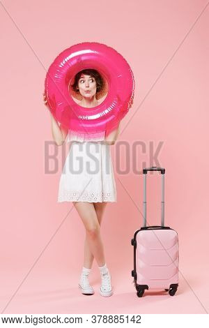 Amazed Tourist Woman In Summer Dress Hat With Suitcase Isolated On Pink Background. Female Traveling
