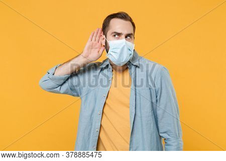 Curious Young Man In Sterile Face Mask Posing Isolated On Yellow Wall Background In Studio. Epidemic