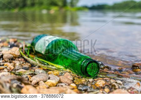 A Glass Bottle Thrown Ashore Pollutes The Environment And Harms Nature