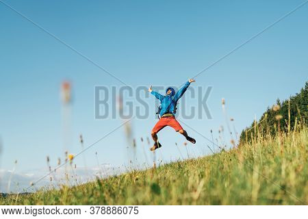 Backpacker Traveler Emotionally Jumping Over Green Grass Mountain Meadow With Backpack With Wide Ope