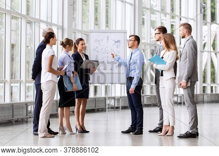 people, planning and strategy concept - business team discussing scheme on flip chart at office