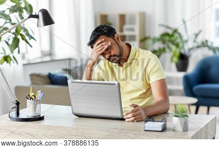technology, remote job and business concept - disappointed indian man with laptop computer working at home office