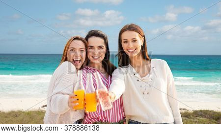 travel, tourism and friendship concept - group of happy young women or female friends toasting non alcoholic drinks over tropical beach background in french polynesia