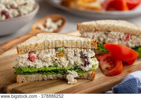 Chicken Salad Sandwich With Lettuce On Whole Wheat Bread Sliced In Half On A Wooden Board