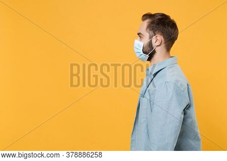Side View Of Young Man In Sterile Face Mask Posing Isolated On Yellow Background In Studio. Epidemic