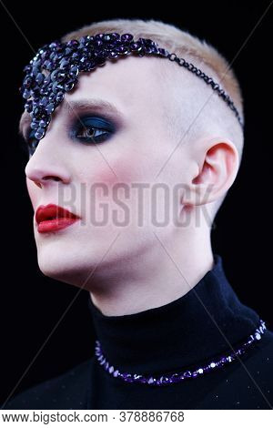 Portrait of a pale young man with women's makeup and with violet jewelry accessories on the head and neck on a black background. Avant-garde fashion.
