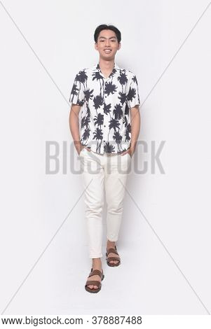 Full body Summer man casual wearing new stylish coconut tree printed t-shirt with white pants and brown shoes with hands holds pocket runway, in studio