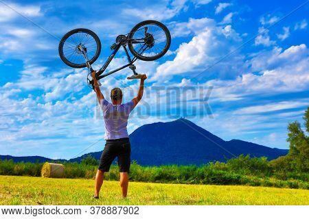 man holding bike behind beautiful landscape and mountain, Puy de Dome- Success, achievement and challenge concept