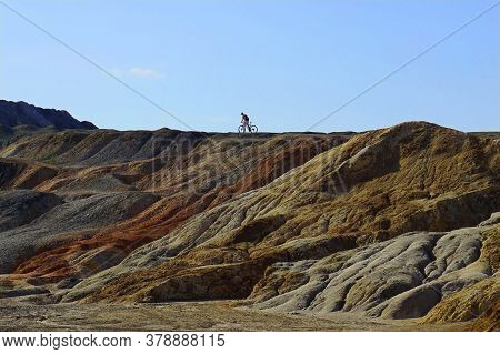 Mounds In A Clay Quarry. In The Distance, The Silhouette Of A Lone Cyclist Against The Sky. Cyclist