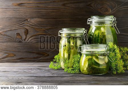 Healthy Fermented Food. Three Glass Jars Of Homemade Fermented Cucumbers With Garlic, Dill And Peppe