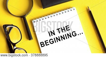 In The Beginning Text, Inscription, Phrase Is Written In A Notebook That Lies On A Yellow Table. Bus