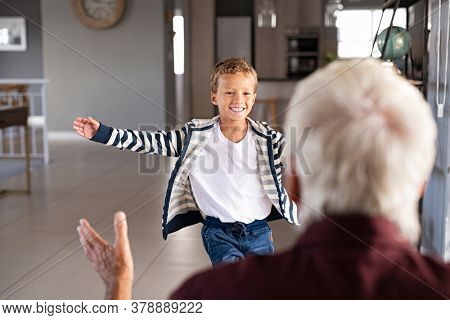 Joyful boy running to hug his old grandfather after school. Happy smiling grandson running and hugging grandparent at home. Senior man and child run to each other with open arms.