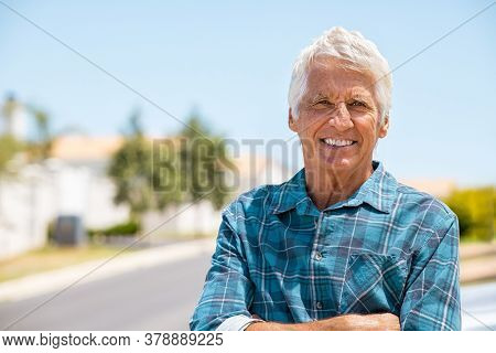 Retired old man standing outdoor with folded arms smiling and looking at camera. Successful mature man relaxing outdoor with copy space. Portrait of happy senior grandfather big grin on face.