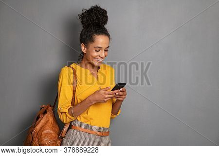 Young beautiful african woman with leather backpack standing on grey wall while using smartphone. Stylish latin girl isolated against gray background checking mobile phone with copy space.