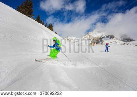 Two Kids 10 Years Old Racing Fast Down The Track On Sunny Day In Alpes Mountains In Colorful Outfit