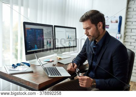 Preparing Financial Report. Young Focused Businessman Or Financial Analyst Sitting At His Workplace