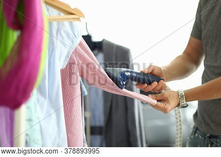 Man Holds Steamer In His Hands And Ironing Shirt On Hanger. Himchitska At Home Concept