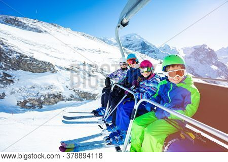 High Portrait Of Four Happy Kids In Vivid Ski Outfit Lifting On Chairlift On The Mountain Together A
