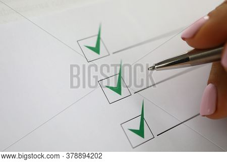 Womans Hand Holds Pen And Marks Green Check Marks In Document. Interviewing Questionnaire Concept