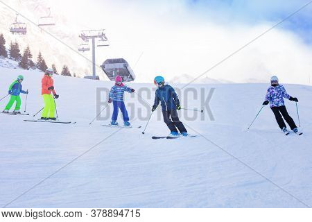 Class Group Of Kids In Ski School Move One After Another On Alpine Slope Learning