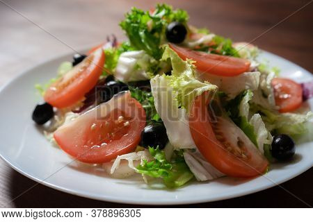 Healthy Food Concept. Vegetable Salad With Green Lettuce, Red Tomatoes And Black Olives. Colorful Na