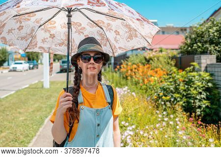 A Woman Stands On A Green Street In A Straw Hat, Glasses And An Umbrella, Protecting Herself From Th