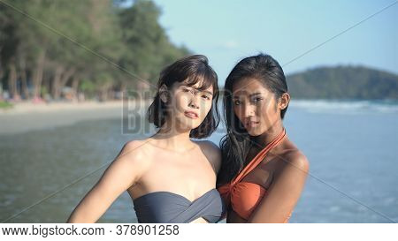 Travel Concept. An Asian Woman In A Bikini Is Watching The Camera On The Beach. 4k Resolution.