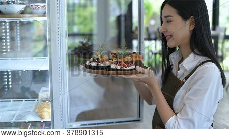 Coffee Shop Concept. An Asian Woman Is Putting The Cake In The Freezer. 4k Resolution.