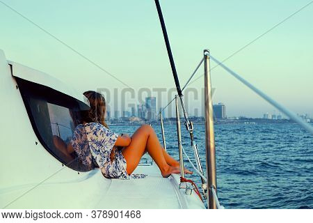 Young Woman In A Dress Sits On The Deck Of A Sailing Yacht. Back View Of Woman In Blue Dress Enjoyin