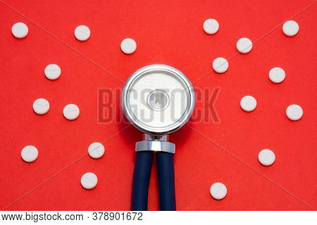 Head Of Stethoscope Is On Red Background Surrounded By Pills Or Tablets With Ornament Of Polka Dots.