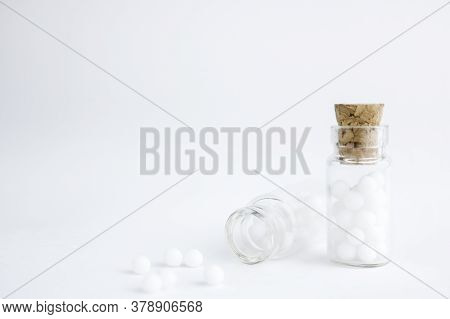 Homeopathic Globules And Glass Bottle On White Background. Alternative Homeopathy Medicine Herbs, He