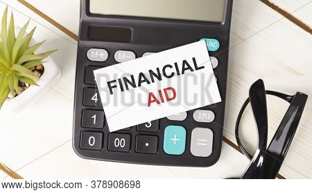 Financial Aid Text Written On Notepad With Glasses