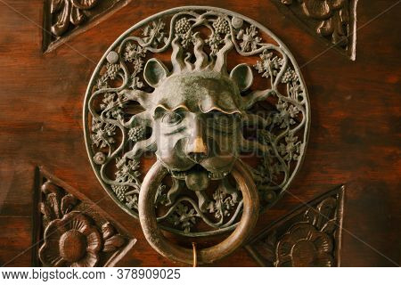 Antique Door Handle On A Wooden Door With Patterns In The Form Of The Face Of A Mythical Character I