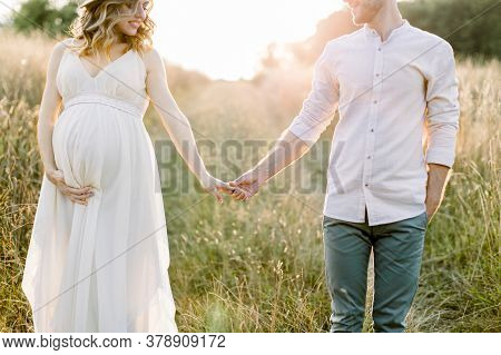 Young Happy Romantic Pregnant Couple Walking In Wild Field In Summer Day. Pregnant Woman In White Dr