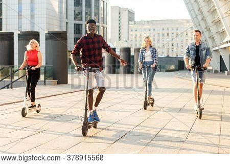 Interracial Group Of Friends Ride Electric Scooters In The City, Multiracial Youth Use Electric Vehi