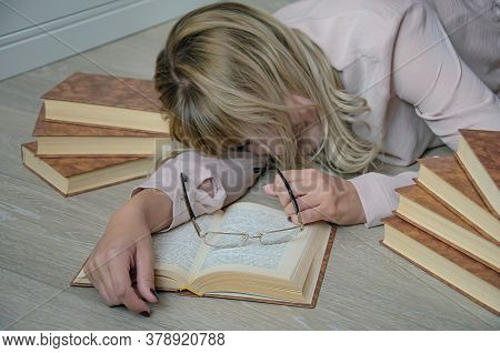 Young Blonde Woman Is Surrounded By Books Had Fallen Asleep On The Floor While Studying. Glasses On