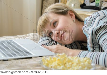 Young Blonde Woman Lies With Popcorn On The Bed And Watches A Movie On A Laptop. A Woman Smiles And