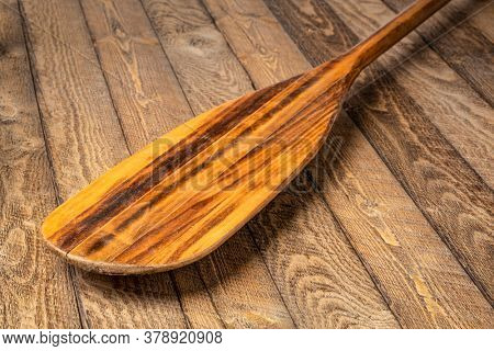 blade of old wooden canoe paddle  against weathered wood background