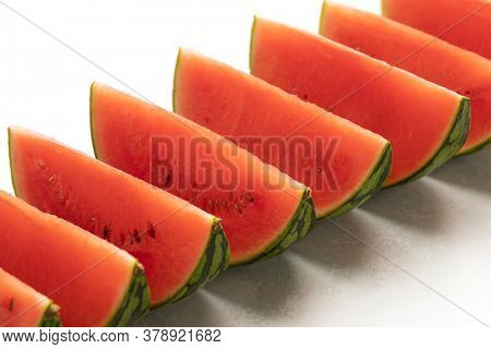 Fresh ripe red watermelon wedges in a row close up