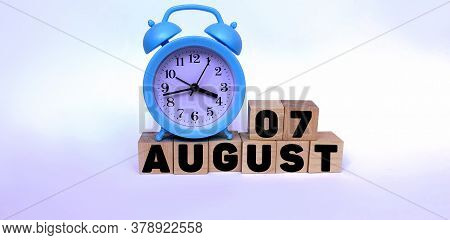 August 7.august 7 On Wooden Cubes On A White Background.blue Watch.photos For The Holiday .the Last